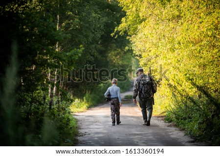 Father and son together hunting together. Walking the road in a forest.