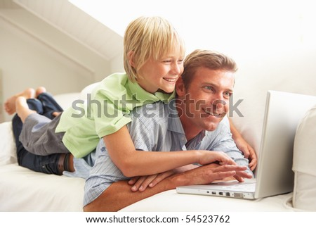 Father And Son Using Laptop Relaxing Sitting On Sofa At Home