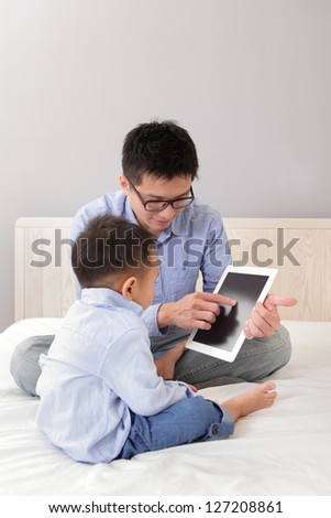 Father and son using tablet pc and sitting on white bed in the bedroom at home, asian people
