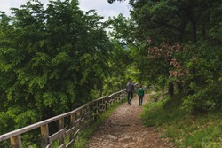 Father and son walking down a mountain path. Concept of friendship, affection and spending time together.