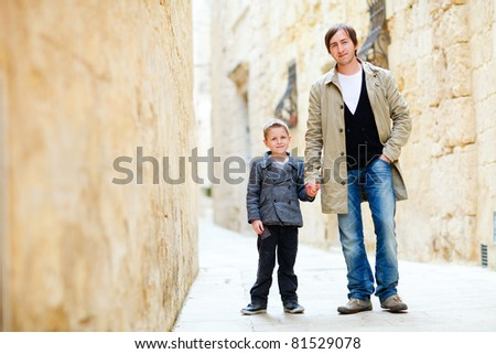 Father and son walking in city along narrow street