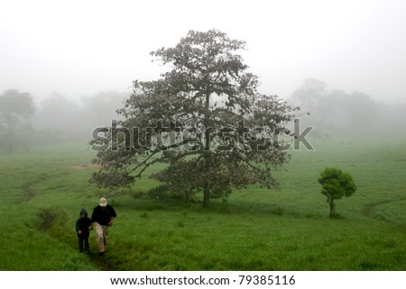 Father and son walking through a field in the Galapagos Islands