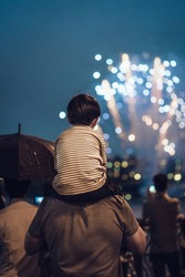 Father and son watching a fireworks festival.