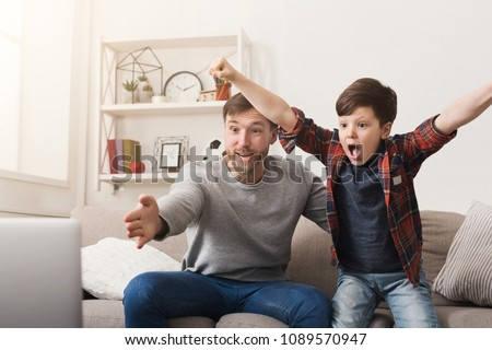 Father and son watching football on TV at home. Emotional man and little boy cheering their favorite team, family enthusiasm, copy space