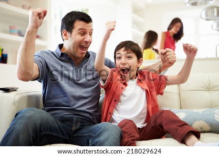 Father And Son Watching Sports On TV - Shutterstock ID 218029624