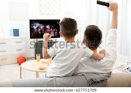 Father and son watching television at home. Leisure and entertainment concept