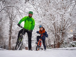 Father and son with bicycles in a winter park. Father explains how to ride a bike. Weekend in the winter park