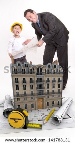 Father and son with blueprints and a building