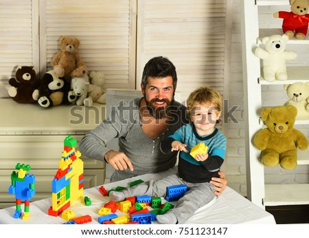 Father and son with happy faces make house with colored bricks. Family and childhood concept. Dad and kid build of plastic blocks. Man with beard and boy play near toys and wooden wall on background #751123147