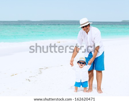 Father and son with panama hats and sunglasses stand on white sandy beach on Maldives