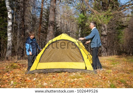 father and son with tent in autumn forest