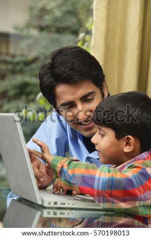 father and son work at laptop