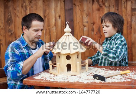 Father and son working on bird house together polishing it with sand paper - stock photo