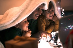 Father and sons shopping online on the bed at winter evening