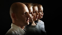 Father and sons, the concept of genetics and heredity. Young man and sons of different ages, portrait in profile on black background
