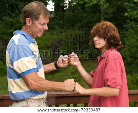 Father and teen son double fist-bumping