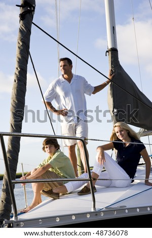 Father and teenage children relaxing on sailboat at dock on sunny day