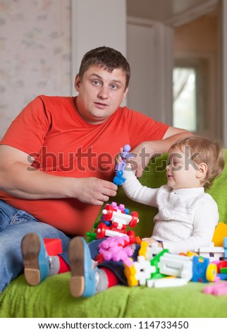 father and  three-year child plays with meccano set in home interior