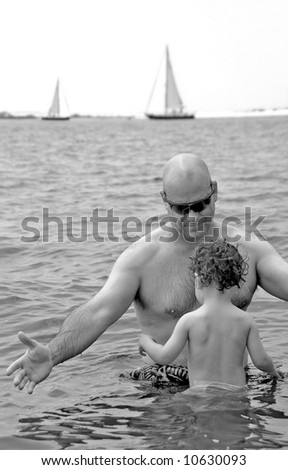 Father and toddler son swimming in ocean water with sailboats in distance