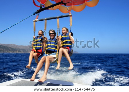 Father and Twin Daughters Parasailing Against a Blue Summer Sky.