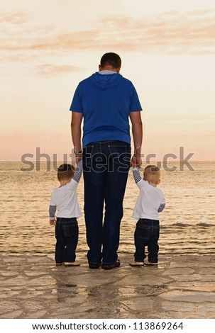 father and twins to the sea at sunset