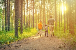 father and two children running in the forest