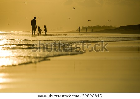 Father and two kids playing on the beach during sunset