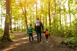 father and two kids with backpack hiking in forest. Social Distancing. Digital detox. Staycations, hyper-local travel,  family outing, getaway, natural environment