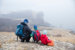 father and two kids with backpack hiking in the mountains on the autumn day. Social Distancing. Digital detox. Staycations, hyper-local travel,  family outing, getaway, natural environment