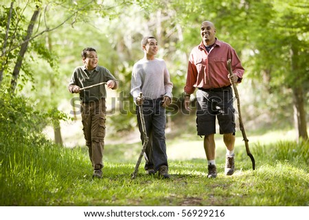 Father and two sons hiking on trail in woods and talking - stock photo
