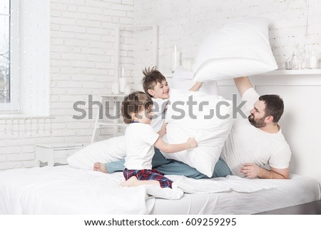 Father and two sons making pillow fight in bed