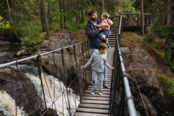 father and two sons walking over rope bridge in the forest. A waterfall under the bridge. Active life concept. Image with selective focus