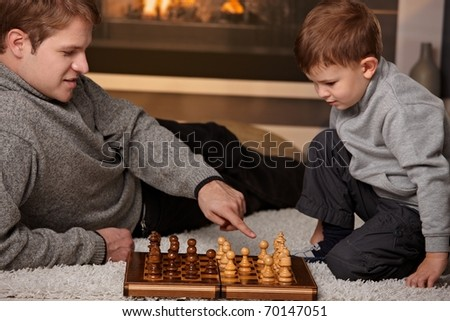 Father and 4 years old boy playing chess at home in a cold winter day.?