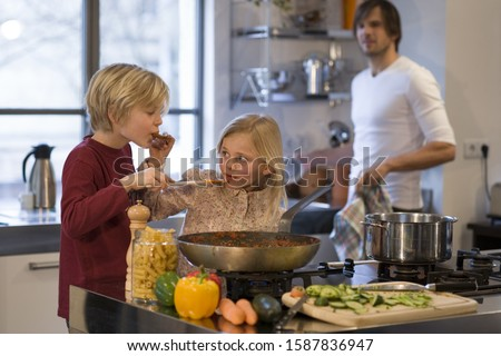 Photo of Father and young children cooking in kitchen