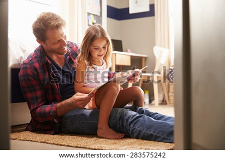 Father and young daughter reading together