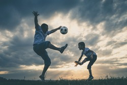 Father and young little boy playing in the field  with soccer ball. Concept of sport.