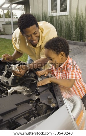 Father and young son inspecting car engine outside house