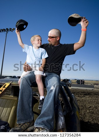 Father and young son waving ball caps in air