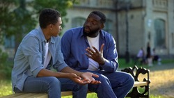 Father arguing teenage son sitting on campus bench, puberty age difficulties