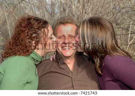 father being kissed by his daughters