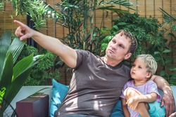 Father blond son sit look far away, dad show with finger. Daddy gently hugs boy child. Bright sun beams light leaves garden terrace. Happy childhood, fatherhood love feelings, fathers day, education