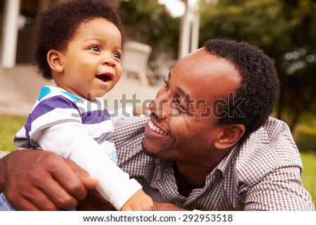 Father bonding with his toddler son in a garden