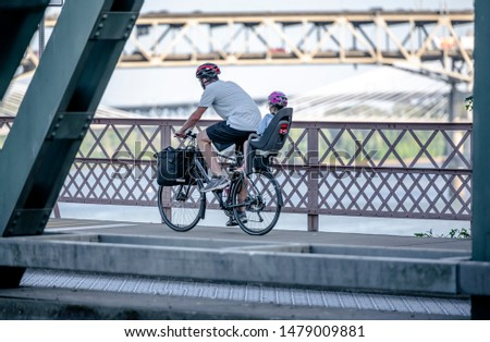 Father carries a little daughter on a bicycle in a special child seat. The use of a bicycle as the main transport for many enthusiasts has grown from a hobby into vital necessity