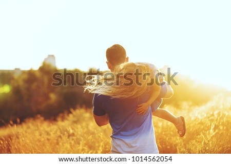 Father carries daughter on shoulder. They walk around the field of ears. Against the setting sun. Shooting from the back. People are unrecognizable #1014562054