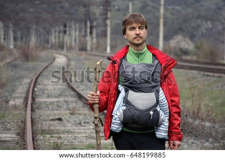 Father carries his infant son in a baby carrie on the railway tracks, Dilijan National Park, Armenia. #648199885