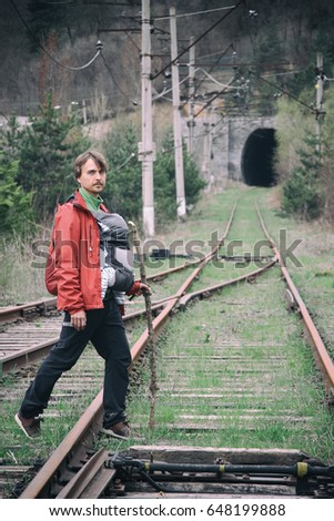 Father carries his infant son in a baby carrie on the railway tracks, Dilijan National Park, Armenia. #648199888