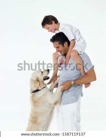 Father carrying child on his shoulders, dog jumping up