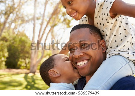 Father Carrying Children On Shoulders As They Walk In Park #586579439