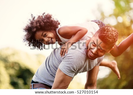 Father carrying daughter on back outdoors