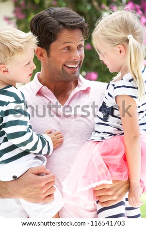 Father Carrying Son And Daughter Outdoors